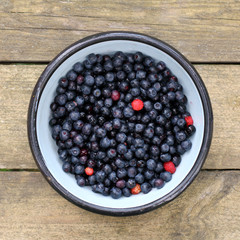 plate with fresh berries/ flat planning, forest blueberries in a bowl on a wooden background, top view