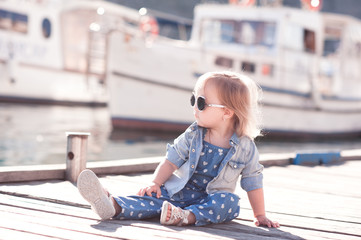 Stylish baby girl 2-3 year old wearing trendy denim clothes sitting on wooden sea pier outdoors. Looking away. Childhood.