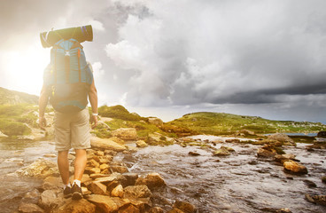 Hiker man with backpack crossing a river. Wall mural