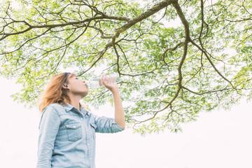 young beautiful  woman drinking water at summer green park.