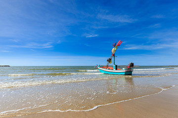 Small fishing boat on the beach with blue sky