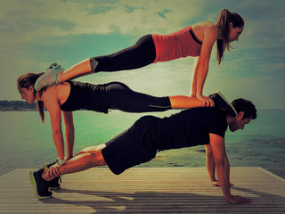 One Man And Two Women Doing Fitness Tricks