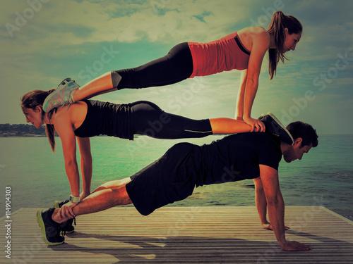 Groupe de personnes faisant une figure de fitness: pompes à trois ...