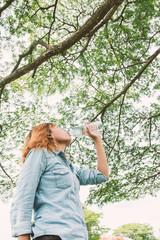 Woman life : young beautiful woman drinking water at  green park