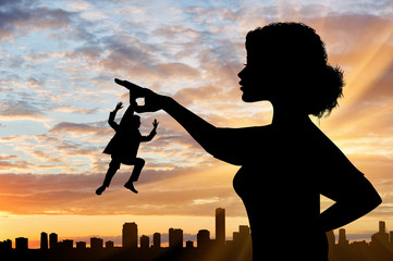 Silhouette feminist holds in his hand the little man against the backdrop of the cityscape