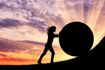 Silhouette of a strong woman pushing a stone up.