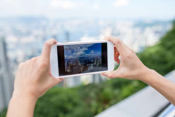 Woman taking photo on city view of Hong Kong with cellphone