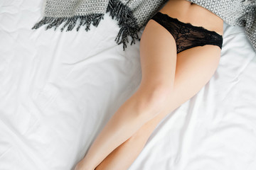 Top view on unrecognizable sexy woman legs in black lace ingerie lying on white bed flat lay.