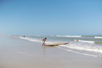 Man pushing a traditional canoe in island of Madagascar
