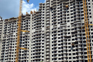 New high-rise modern apartment building construction in process ob bright sunny day front view horizontal