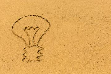 Light bulb drawn by hand on a golden sandy sea beach.