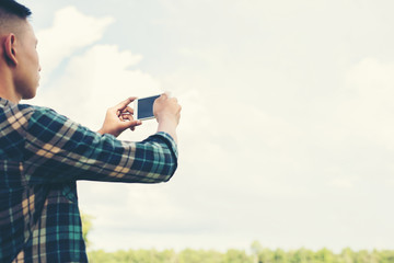 Young hipster man using smartphone taking the landscape photogra