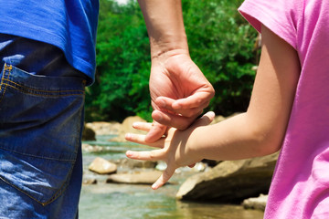 Dad and daughter have joined hands on the river bank