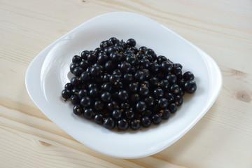 Созревшая черная смородина на белой тарелке