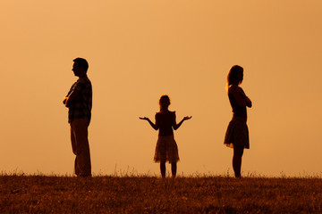 Silhouette of a angry husband and wife  on each other with their confused daughter standing in the middle.