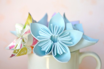 Origami flower in white ceramic cup