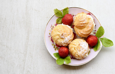 Cream puffs or profiterole filled with whipped cream served with strawberries on a stone grey board for text