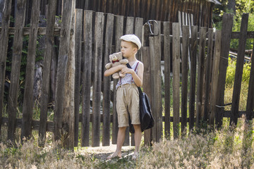 boy with a briefcase and a teddy bear in a village on the nature