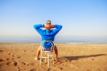 Man relax seating on chair at beach.