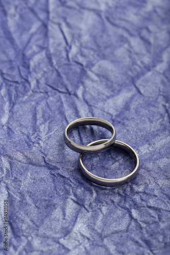 quotsilver wedding rings on a purple paper backgroundquot stock
