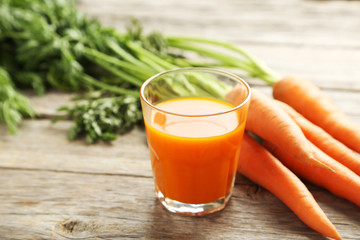 Fresh carrot juice in glass on a grey wooden table