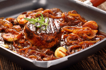 Grilled pork chop with onion on the pan on wooden background