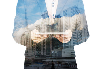 Double exposure of a businessman and a city using a tablet over