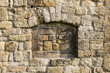 Wall made of natural sandstone rough fractured surfaces, laid as a brick. Stone wall background texture. Taupe cut block sandstone old wall with grass