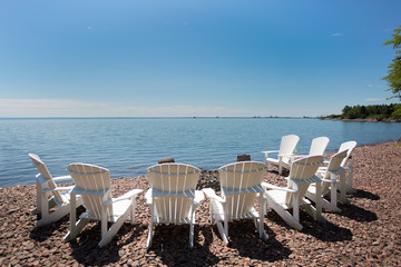 Beach chairs arranged in a semicircle on the shore of Lake Superior