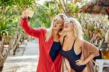 Outdoor lifestyle portrait of two female friends taking photos w