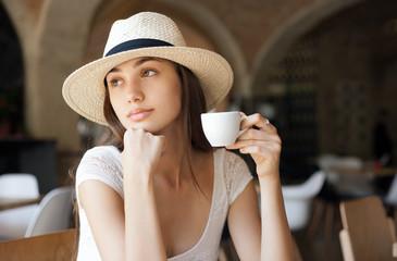 Elegant brunette beauty having coffee.