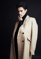cool real young handsome man in coat on black background posing, fashion people concept