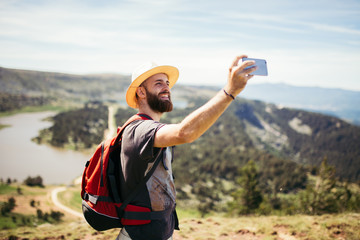 Man taking a selfie in nature and smiling