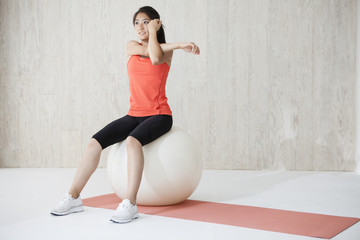 Young woman is doing the arm of the stretch sitting on a balance ball