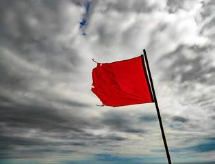 Torn, red warning flag flying under grey skies