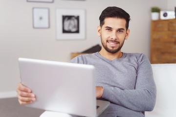 mann sitzt auf dem sofa und arbeitet am laptop