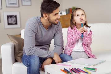 nachdenkliches kleines mädchen malt ein bild mit seinem papa