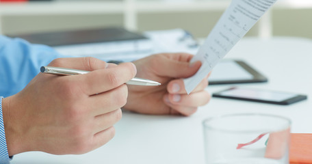 Male hands holding a silver pen and paper closeup. Businessman making notes. Business job offer, financial success, certified public accountant concept.