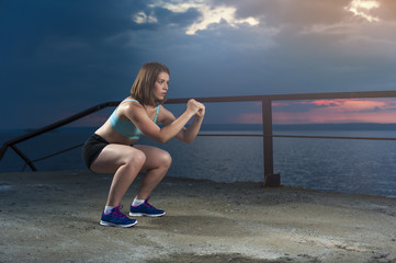 Young caucasian woman exercising on sea pier