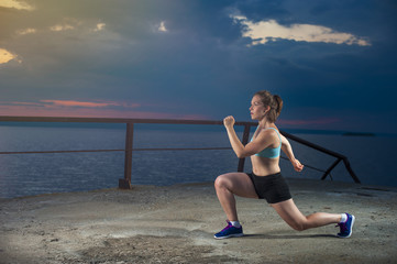 Healthy fit woman doing lunges on sea pier