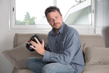 Handsome Man adjusting his camera at home
