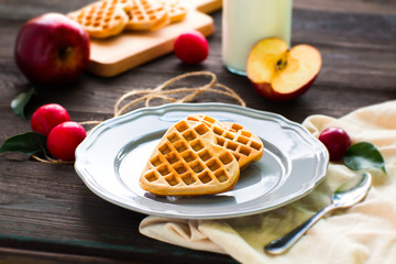 Heart-shaped waffles with apples and cherry-plums on a dark wooden background