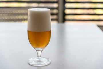 Glass of lager beer on white table