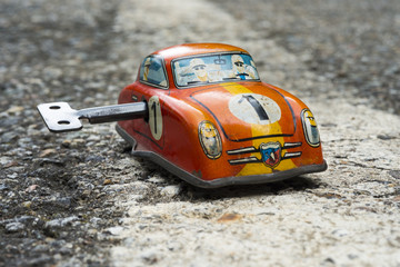 Clockwork toy car on asphalt background