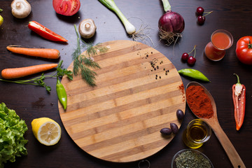 Cutting board and vegetables and spices around ready for prepare a recipe. photo from above on the table
