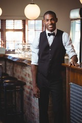 Portrait of bartender standing at bar counter