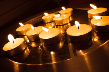Group of pray candles burn on a metal stand