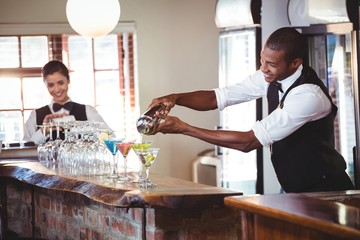 Bartender pouring a drink from a shaker to a glass