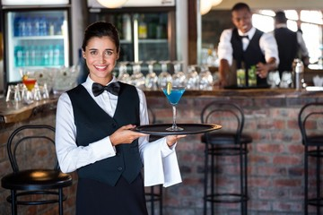 bartender holding serving tray with glass of cocktail