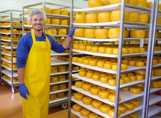 Keuken foto achterwand Bakkerij Handsome cheesemaker is checking cheeses in his workshop storage.